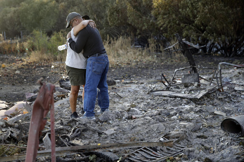 Justo and Bernadette Laos hug while looking through the charred remains of the home they rented that was destroyed by the Kincade Fire near Geyserville, Calif., Thursday, Oct. 31, 2019. The fire started last week near the town of Geyserville in Sonoma County north of San Francisco. (AP Photo/Charlie Riedel)