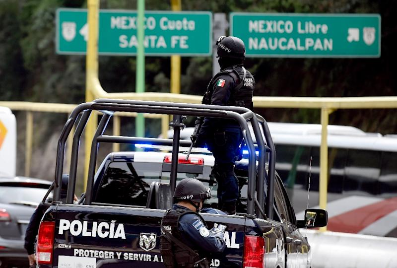 Police stand guard at a checkpoint on the road connecting Toluca with Mexico City on July 14, 2015
