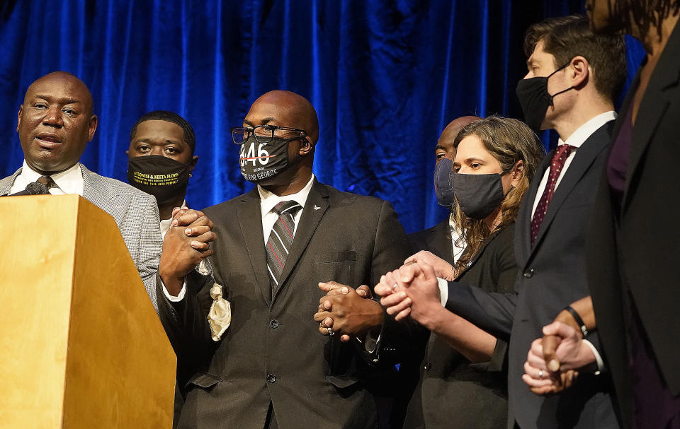 Floyd family attorney Ben Crump, left, asked all to clasp hands during a press conference to announce a $27 million civil lawsuit settlement between the Floyd family and the City of Minneapolis Friday, March 12, 2021, in Minneapolis. Standing next to Crump is Brandon Williams, Floyd's nephew, left to right, Philonise Floyd, Rodney Floyd, both George Floyd's brothers, Lisa Bender, Minneapolis city council president, and Minneapolis Mayor Jacob Frey. (David Joles/Star Tribune via AP)