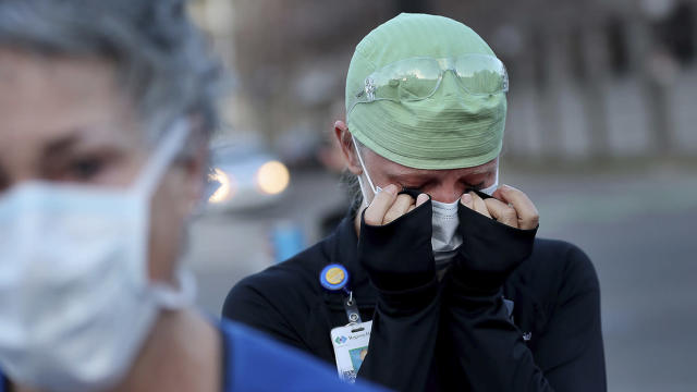 Health care workers at Regions Hospital in St. Paul, Minn., including ER nurse Tamara Hill, come outside to thank Xcel Energy crew members who lined the street to greet health workers on April 22. (David Joles/Star Tribune via AP)