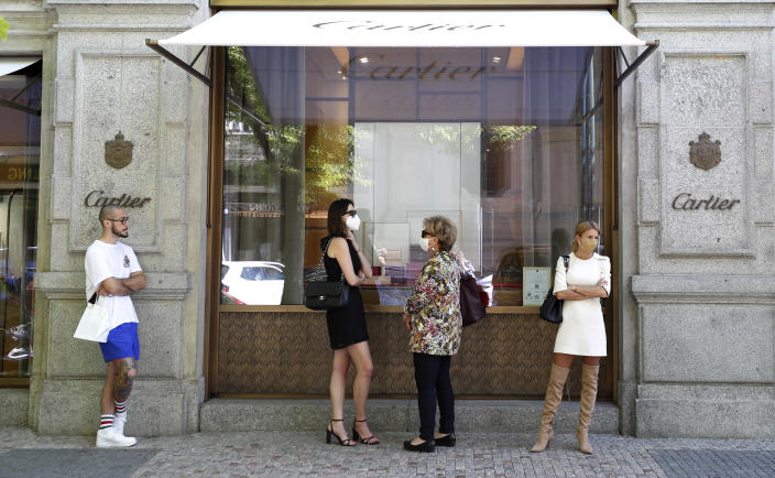 People wait in line in front of a shop in Prague, Czech Republic, Monday, May 10, 2021. The Czech Republic is massively relaxing its coronavirus restrictions as the hard-hit nation pay respect to nearly 30,000 dead. Monday's wave of easing came after the new infections fell to the levels unseen from August when the government failed to react in time to an opposite trend, the growing numbers of infected which later contributed to record numbers of deaths. (AP Photo/Petr David Josek)