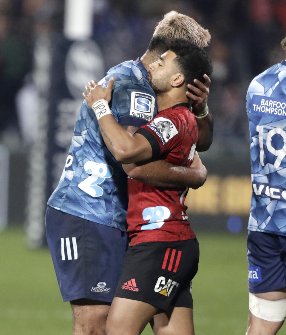 Crusaders Richie Mo'unga, right, and Blues Akira Ioane embrace following the Super Rugby Aotearoa rugby game between the Crusaders and the Blues in Christchurch, New Zealand, Saturday, July 11, 2020. (AP Photo/Mark Baker)