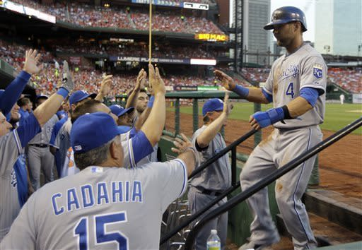 Kansas City Royals' Alex Gordon, right, is congratulated by teammates after scoring on a sacrifice fly by Lorenzo Cain during the fourth inning of a baseball game against the St. Louis Cardinals on Wednesday, May 29, 2013, in St. Louis. (AP Photo/Jeff Roberson)