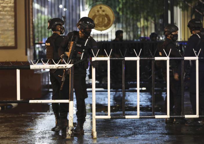 Officers set up a barricade at the gate of the National Police Headquarters following a suspected militant attack in Jakarta, Indonesia, Wednesday, March 31, 2021. A woman entered the Indonesian National Police Headquarters in Jakarta and pointed a gun at several officers before being shot dead by police, in the latest in a series of militant attacks in the world's most populous Muslim nation. (AP Photo/Dita Alangkara)