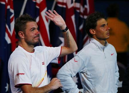 Stanislas Wawrinka of Switzerland waves as he stands next to Rafael Nadal (R) of Spain after winning their men's singles final match at the Australian Open 2014 tennis tournament in Melbourne January 26, 2014. REUTERS/Petar Kujundzic