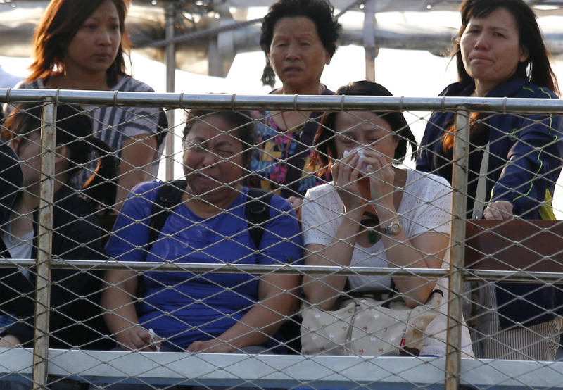 Relatives of the victims cry Tuesday, Oct. 2, 2012 as they pay tribute to the ill-fated people aboard a boat that sank Monday night near Lamma Island, off the southwestern coast of Hong Kong Island. The boat packed with revelers on a long holiday weekend collided with a ferry and sank off Hong Kong, killing at least 36 people and injuring dozens, authorities said. (AP Photo/Vincent Yu)