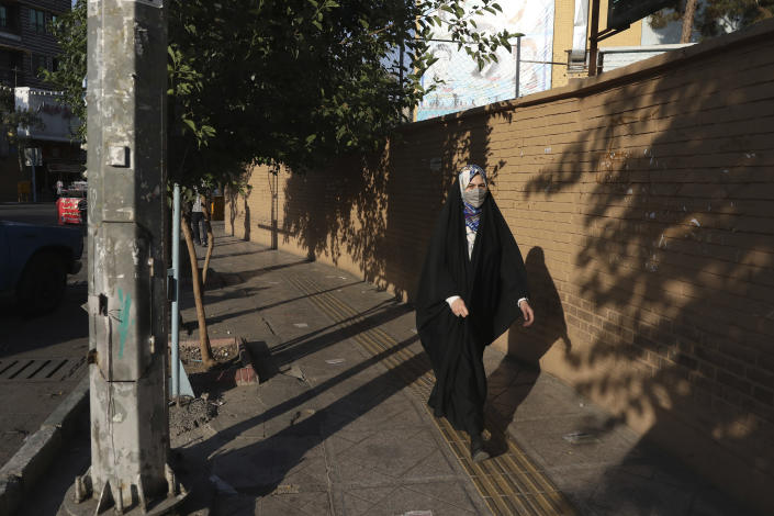 A woman wearing protective face mask to help prevent the spread of the coronavirus walks on a sidewalk in southern Tehran, Iran, Tuesday, July 20, 2021. Iran on Tuesday broke another record in the country's daily new coronavirus cases, even as Tehran and its surroundings went into lockdown, a week-long measure imposed amid another surge in the pandemic. (AP Photo/Vahid Salemi)