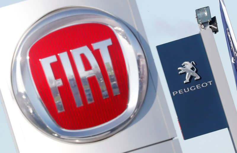 The logos of car manufacturers Fiat and Peugeot are seen in front of dealerships of the companies in Saint-Nazaire