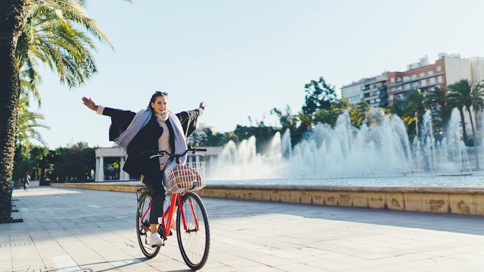 Happy woman with arms outstretched exploring Valencia on bicycle.