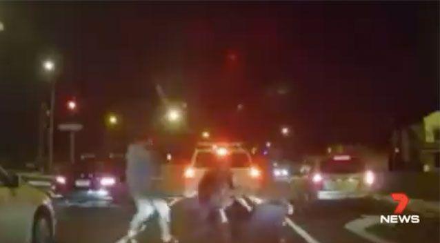 Two more men appear and the four involved in a scuffle in the middle of the road. Source: 7 News
