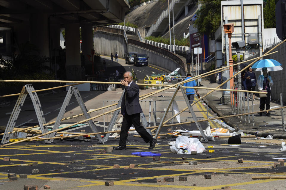 A man crosses in front of a roadblock set up by pro-democracy protesters outside the Hong Kong Baptist University, in Hong Kong, Wednesday, Nov. 13, 2019. Police have increased security around Hong Kong and its university campuses as they brace for more violence after sharp clashes overnight with anti-government protesters. (AP Photo/Vincent Yu)