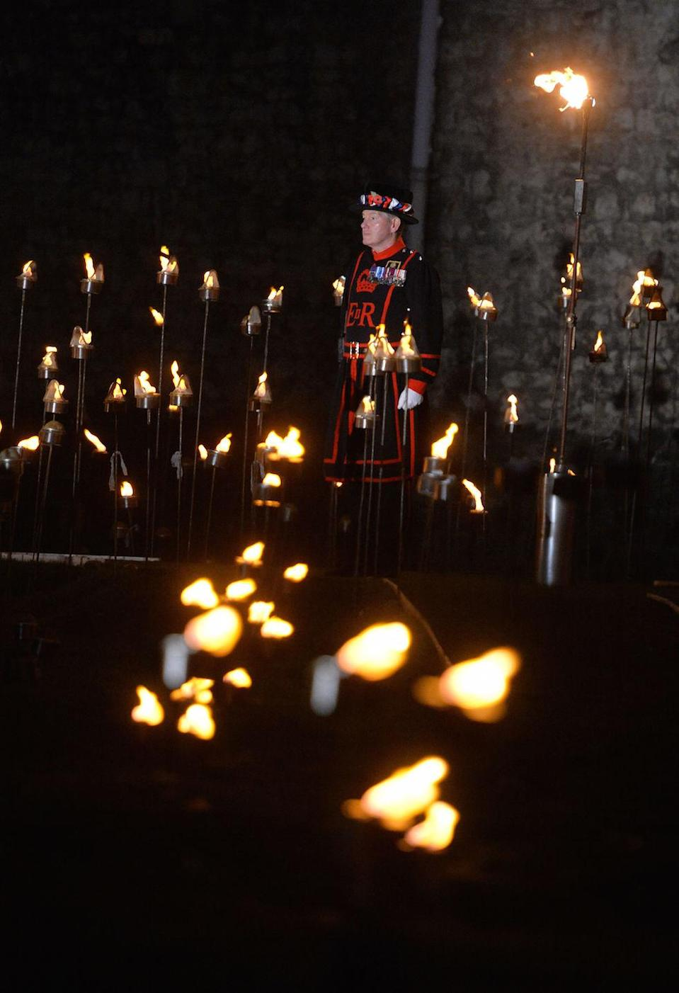 <p>Beefeaters ighting the first of thousands of flames in a lighting ceremony in the dry moat of the Tower of London as part of an installation called Beyond the Deepening Shadow: The Tower Remembers, to mark the centenary of the end of First World War. (Picture: PA) </p>