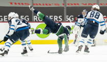 Vancouver Canucks left wing Nils Hoglander (36) falls to the ice after being checked by Winnipeg Jets defenseman Neal Pionk (4) during first-period NHL hockey game action in Vancouver, British Columbia, Sunday, Feb. 21, 2021. (Jonathan Hayward/The Canadian Press via AP)