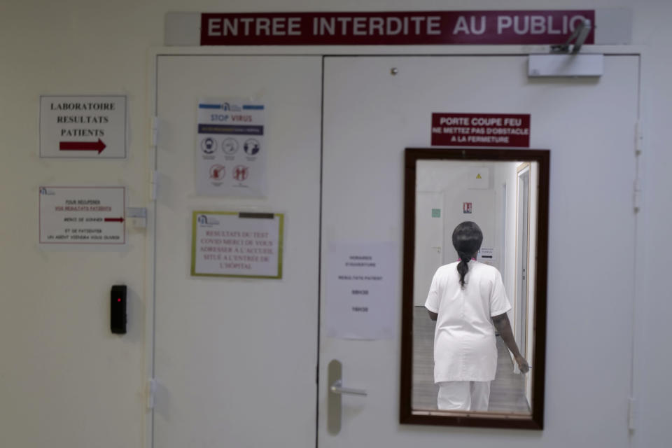 Health lab technician walks in a zone forbidden to public to process test for COVID-19 at the Hospital of Argenteuil, north of Paris, Friday Sept. 25, 2020. France's health agency announced Thursday evening that the country has had 52 new deaths and has detected over 16,000 new cases of coronavirus in 24 hours. (AP Photo/Francois Mori)