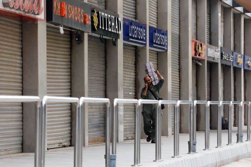 Man walks past closed market during a partial lockdown amid the COVID-19 outbreak in Karachi