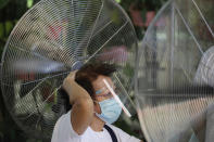 Standing in front of fans, a woman holds her hair as she waits to be inoculated with China's Sinovac COVID-19 vaccine in Quezon city, Philippines on Friday, May 14, 2021. The Philippine president has eased a coronavirus lockdown in the bustling capital and adjacent provinces to fight economic recession and hunger but still barred public gatherings this month, when many Roman Catholic summer religious festivals are held. (AP Photo/Aaron Favila)