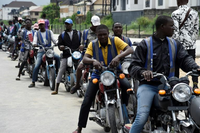 Regular motorcycle taxis queue for custom in Lagos -- helmets and safety kits are absent, and passengers have to haggle over fares