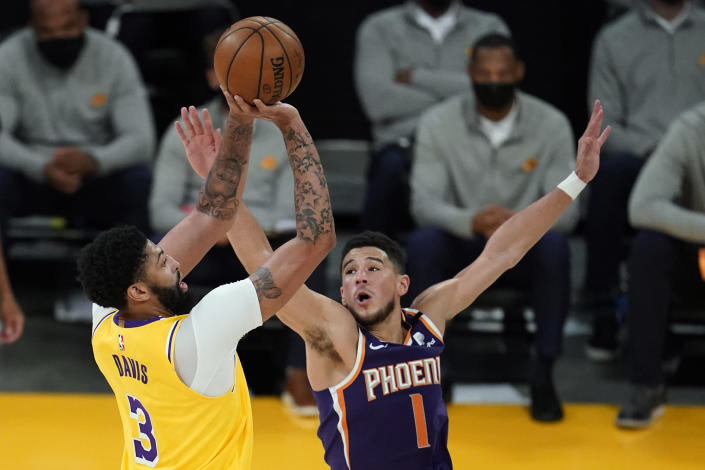 Los Angeles Lakers forward Anthony Davis (3) shoots over Phoenix Suns guard Devin Booker (1) during the first half in Game 3 of an NBA basketball first-round playoff series Thursday, May 27, 2021, in Los Angeles. (AP Photo/Marcio Jose Sanchez)