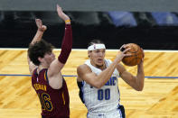 Orlando Magic forward Aaron Gordon (00) looks to pass the ball as he his path to the basket is guarded by Cleveland Cavaliers forward Cedi Osman (16) during the first half of an NBA basketball game, Monday, Jan. 4, 2021, in Orlando, Fla. (AP Photo/John Raoux)