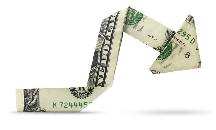 A dollar bill folded into a charting arrow pointing downward, origami-style.