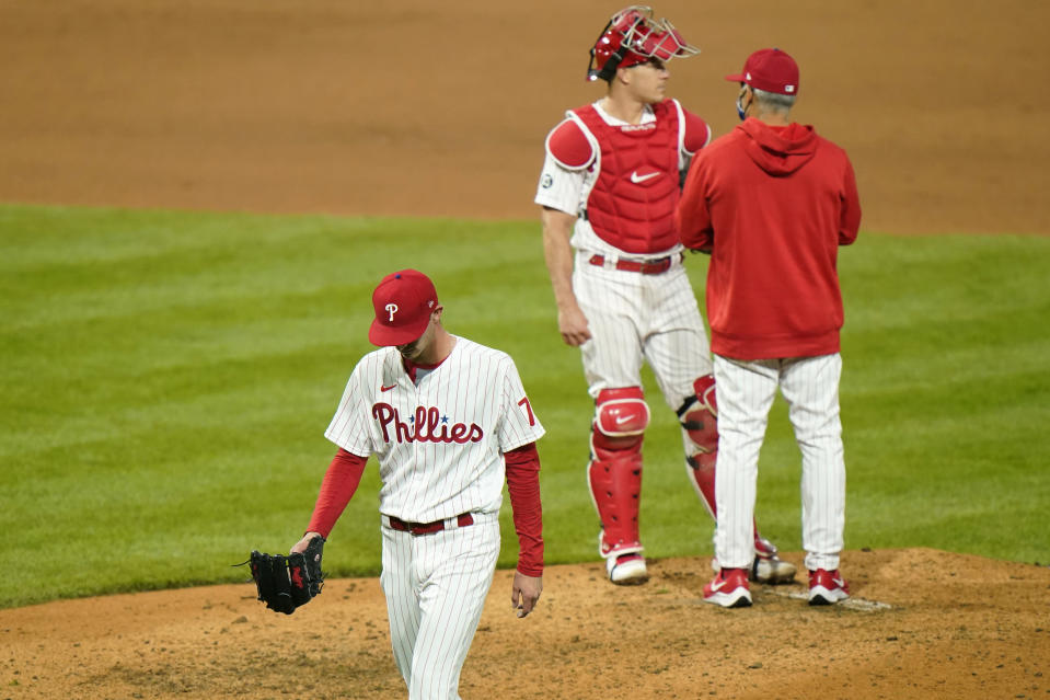 Philadelphia Phillies pitcher Connor Brogdon, left, walks to the dugout after being pulled during the eighth inning of a baseball game against the San Francisco Giants, Tuesday, April 20, 2021, in Philadelphia. (AP Photo/Matt Slocum)