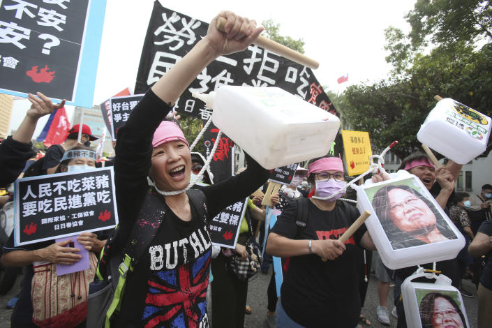 People gather with images of Taiwanese President Tsai Ing-wen for a protest in Taipei, Taiwan, Sunday, Nov. 22. 2020. Thousands of people marched in streets on Sunday demanding the reversal of a decision to allow U.S. pork imports into Taiwan, alleging food safety issues. (AP Photo/Chiang Ying-ying)