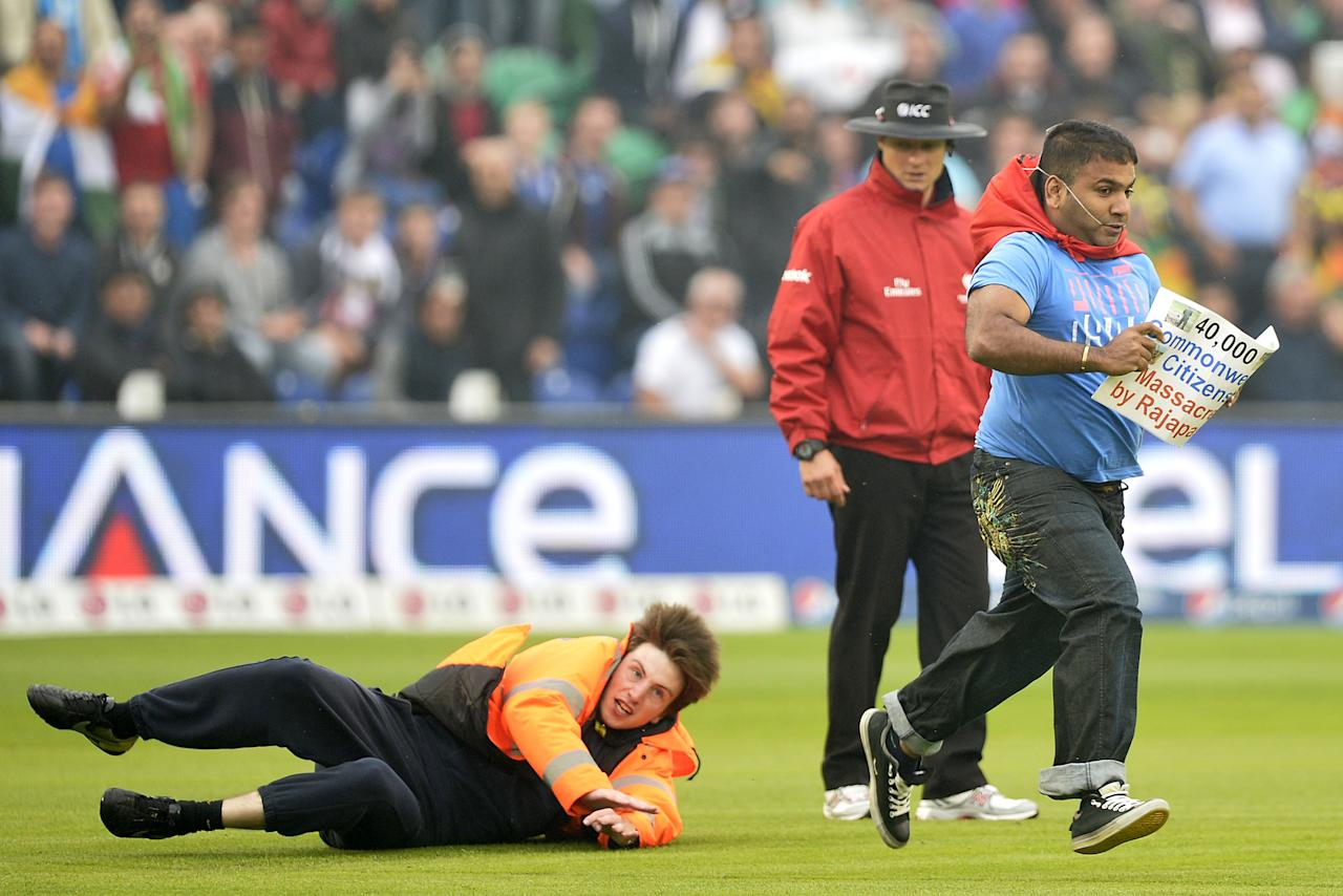 A steward falls as he chases a demonstrator who ran onto the pitch during the 2013 ICC Champions Trophy semi-final cricket match between India and Sri Lanka at the Cardiff Wales stadium in Cardiff on June 20, 2013. AFP PHOTO/ADRIAN DENNIS --  RESTRICTED TO EDITORIAL USE --