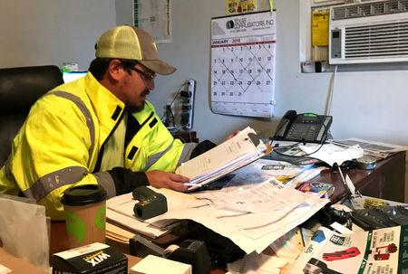 Will Ortega, a 32-year-old supervisor at an infrastructure safety company, reviews budget paperwork in his office in San Antonio, Texas, U.S. February 6, 2018.  Photo taken February 6, 2018.   REUTERS/Lisa Maria Garza