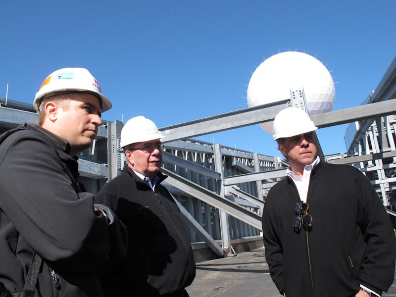 Mitch Olorenshaw, left, whose company built the giant ball atop the Revel casino in Atlantic City N.J.; Cliff Wildgoose, director of engineering and construction for Revel, center; and Mitch Gorshin, right, who designed the ball, discuss it during testing of the device on the casino's rooftop on March 7, 2012. (AP Photo/Wayne Parry)