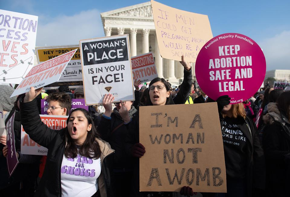 Pro-abortion-rights activists outside the U.S. Supreme Court in Washington, D.C., on Friday hold signs in response to anti-abortion activists participating in the March for Life, an annual event to mark the anniversary of <em>Roe v. Wade</em>. (Photo: Saul Loeb/AFP/Getty Images)