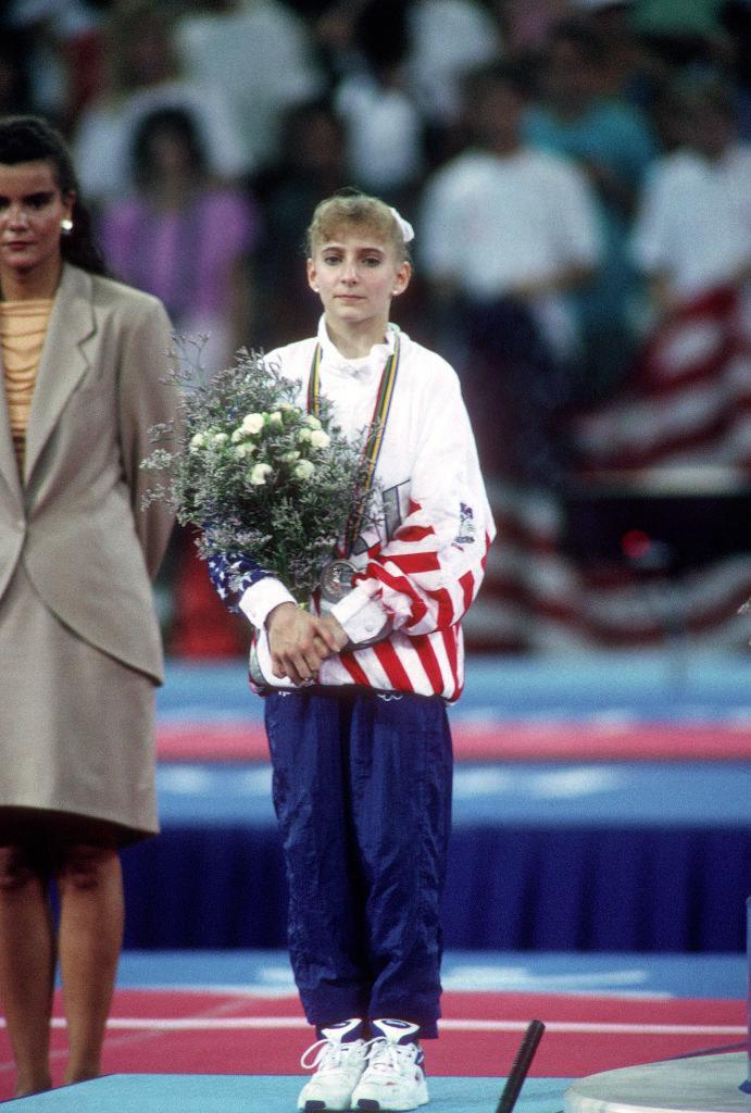 Shannon standing on the platform with her bouquet of flowers during the medal ceremony