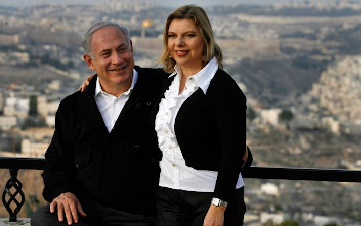 Mr Netanyahu and wife Sara during a stroll along a promenade overlooking the Old City in Jerusalem - Getty Images