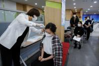 A nursing home worker has the temperature checked by a medical staff before receiving the AstraZeneca COVID-19 vaccine at a health care centre, as South Korea starts a vaccination campaign against the coronavirus disease (COVID-19), in Seoul