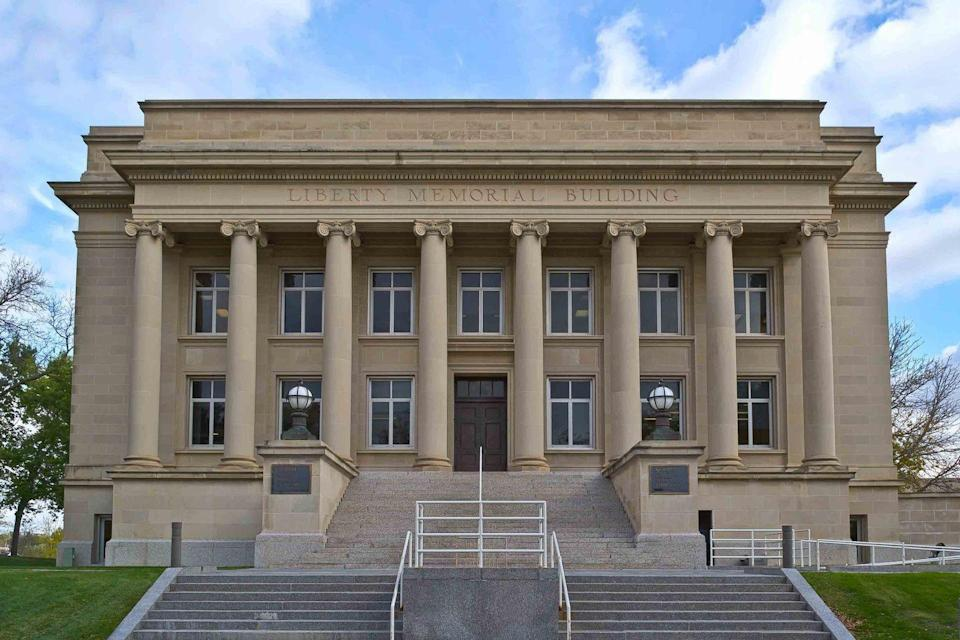 """<p>The <a href=""""http://www.library.nd.gov"""" rel=""""nofollow noopener"""" target=""""_blank"""" data-ylk=""""slk:North Dakota State Library"""" class=""""link rapid-noclick-resp"""">North Dakota State Library</a> is quite stately with its classical stone architecture and ornamental bronze doors. Built in 1924 on Bismark's Captiol Mall, it's also surrounded by an open field lined by gorgeous elm trees. <br></p>"""