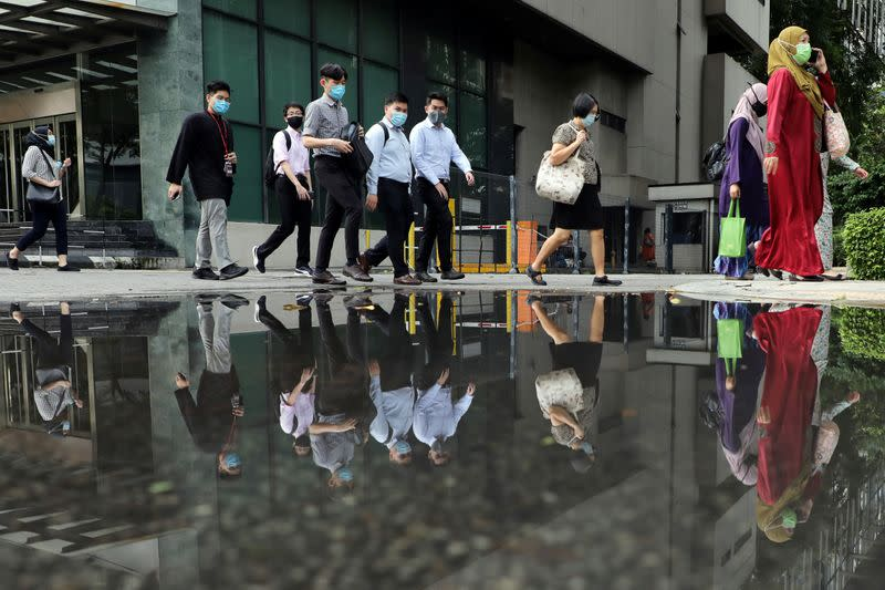 People wearing protective masks are reflected in a water puddle as they cross a street, amid the coronavirus disease (COVID-19) outbreak in Kuala Lumpur