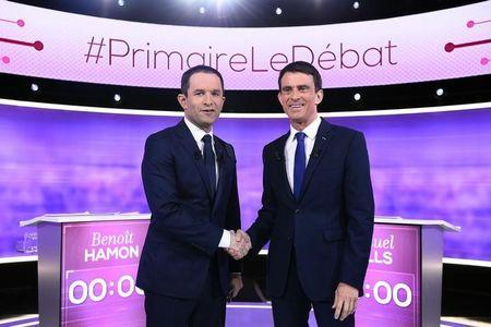 French Socialist party politicians, former prime minister Manuel Valls and former education minister Benoit Hamon shake hands as they  attend the final debate in the French left's presidential primary election in La Plaine-Saint-Denis