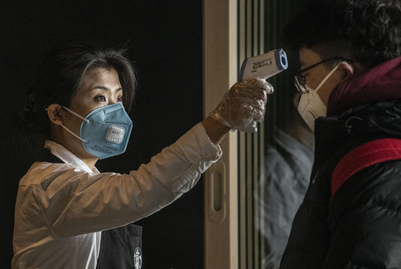 BEIJING, CHINA - JANUARY 30: A Chinese worker from Starbucks checks the temperature of a customer at Beijing Capital Airport on January 30, 2020 in Beijing, China. The number of cases of a deadly new coronavirus rose to over 7000 in mainland China Thursday as the country continued to lock down the city of Wuhan in an effort to contain the spread of the pneumonia-like disease which medicals experts have confirmed can be passed from human to human. In an unprecedented move, Chinese authorities put travel restrictions on the city which is the epicentre of the virus and neighbouring municipalities affecting tens of millions of people. The number of those who have died from the virus in China climbed to over 170 on Thursday, mostly in Hubei province, and cases have been reported in other countries including the United States, Canada, Australia, Japan, South Korea, and France. The World Health Organization has warned all governments to be on alert, and its emergency committee is to meet later on Thursday to decide whether to declare a global health emergency. (Photo by Kevin Frayer/Getty Images)
