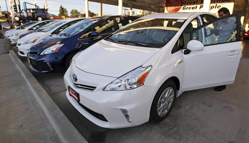 File-This Jan. 26, 2012 file photo shows an employee parks a Toyota gas-electric hybrid automobile in a row of similar cars at a dealership in Los Angeles. The governors of eight states including California and New York pledged Thursday to get 3.3 million zero-emission vehicles on roadways by 2025 in an effort to curb greenhouse gas pollution. (AP Photo/Reed Saxon)