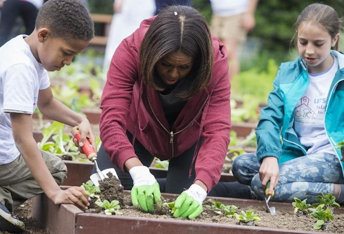 US First Lady Michelle Obama talks with children as they plant vegetables in the White House Kitchen Garden on the South Lawn of the White House in Washington, DC, April 15, 2015 (AFP Photo/Saul Loeb)