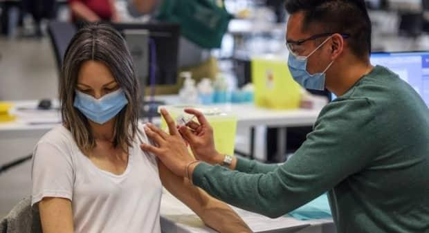 Kathryn Kazmerik, 32, receives her COVID-19 vaccine at the Telus Convention Centre mass-vaccination in Calgary on April 19, 2021. (Leah Hennel/AHS - image credit)