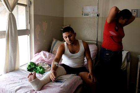 Denis Navarro (R) stands next to her husband Jesus, while he lies on a bed at the Universitary Hospital in Merida, Venezuela June 17, 2016. REUTERS/Marco Bello