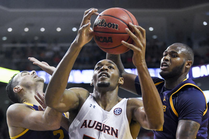 Auburn center Austin Wiley (50) snags a rebound over Lipscomb guard Andrew Fleming (2) and center Ahsan Asadullah (23) during the second half of an NCAA college basketball game Sunday, Dec. 29, 2019, in Auburn, Ala. (AP Photo/Julie Bennett)