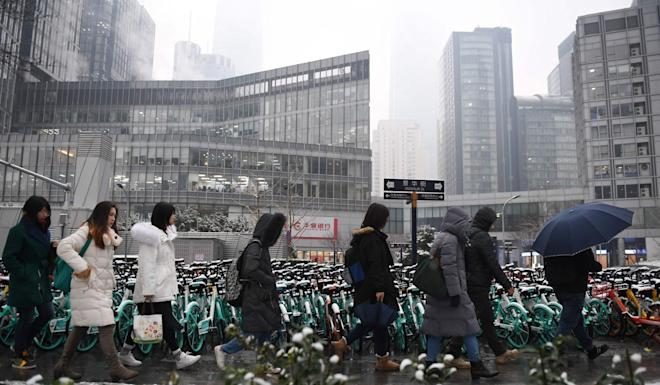 Office workers walk past buildings in Beijing's central business district. China is set to surpass the US as the biggest insurance market by 2030s, according to Zurich Re. Photo: AFP
