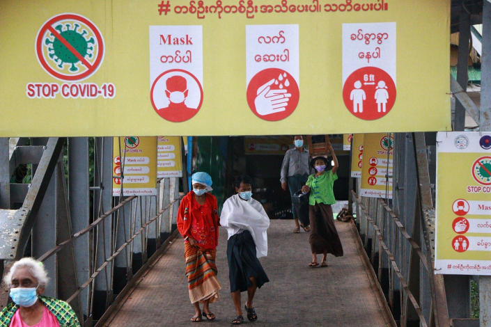 """Ferry passengers wearing face masks walk past """"Stop COVID-19"""" posters and banner at the Pansodan jetty in Yangon, Myanmar Tuesday, July 27, 2021. (AP Photo) ]"""