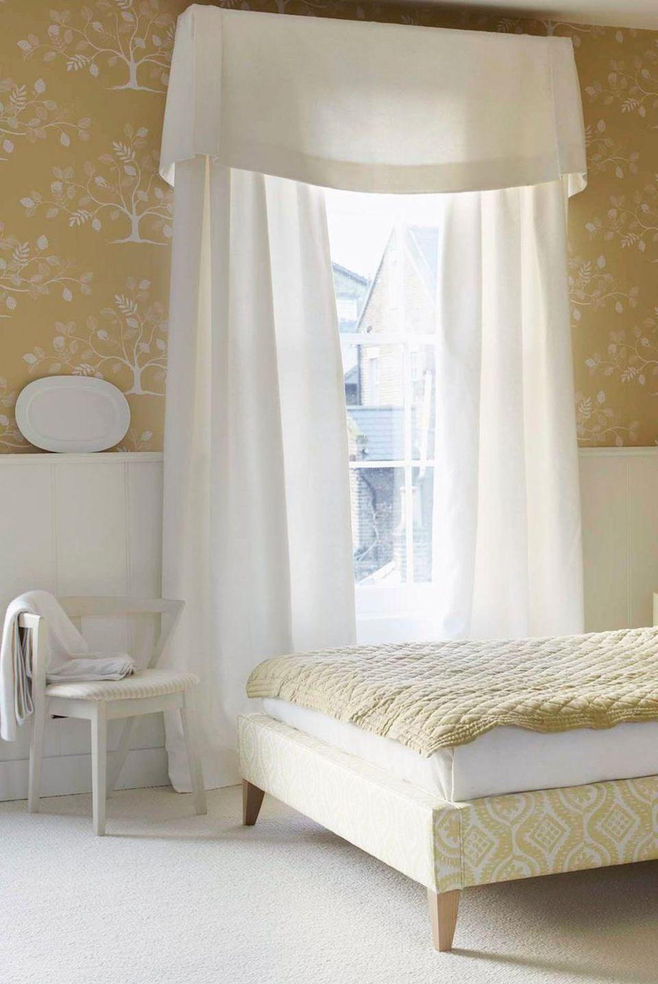 <p>Long, lightweight window treatments — perfect for maximizing natural light — play up this bedroom's romantic flair.</p>