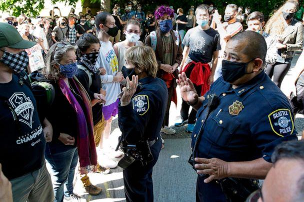 PHOTO: Seattle Police Assistant Chief Deanna Nollette and Assistant Chief Adrian Diaz are blocked by protesters from entering the newly created Capitol Hill Autonomous Zone (CHAZ) in Seattle, June 11, 2020. (Jason Redmond/AFP via Getty Images)