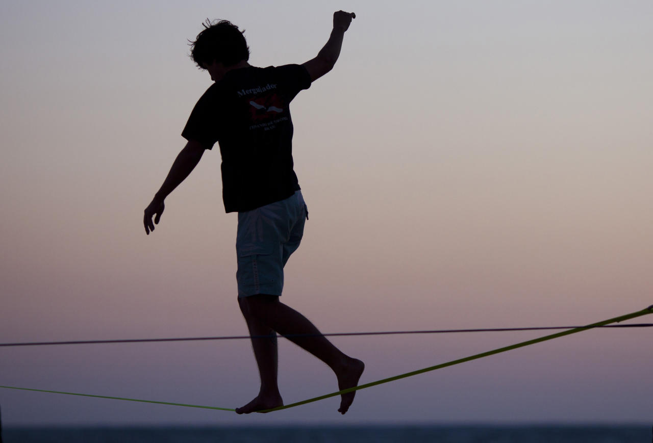 Silhouetted against a dusk sky, a man practices walking on a slackline at Ipanema beach in Rio de Janeiro, Brazil, Thursday Aug. 4, 2011. (AP Photo/Felipe Dana)