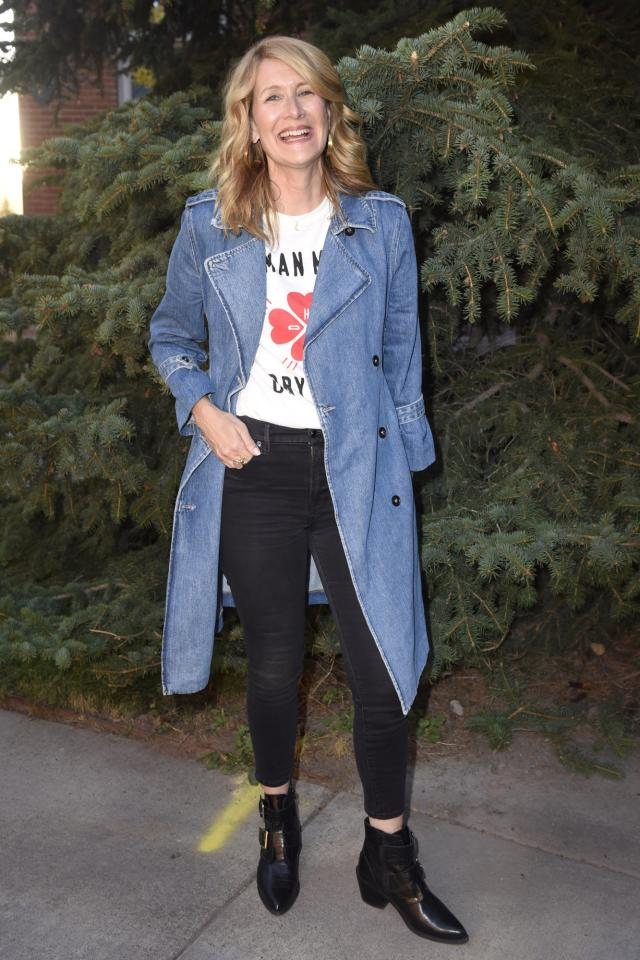 in a long denim coat, white graphic t-shirt, black skinny jeans and black ankle boots with buckle details at the Telluride Film Festival in Colorado.