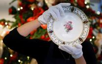 Employee of Sotheby's poses with a piece from the Napoleon I dinner service at Thomas Goode and Co ahead of their Sotheby's auction, in London