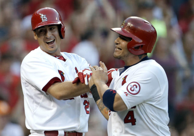 St. Louis Cardinals' Allen Craig, left, and Yadier Molina celebrate after scoring on a two-run single by Matt Adams during the second inning of a baseball game against the Philadelphia Phillies on Wednesday, July 24, 2013, in St. Louis. (AP Photo/Jeff Roberson)